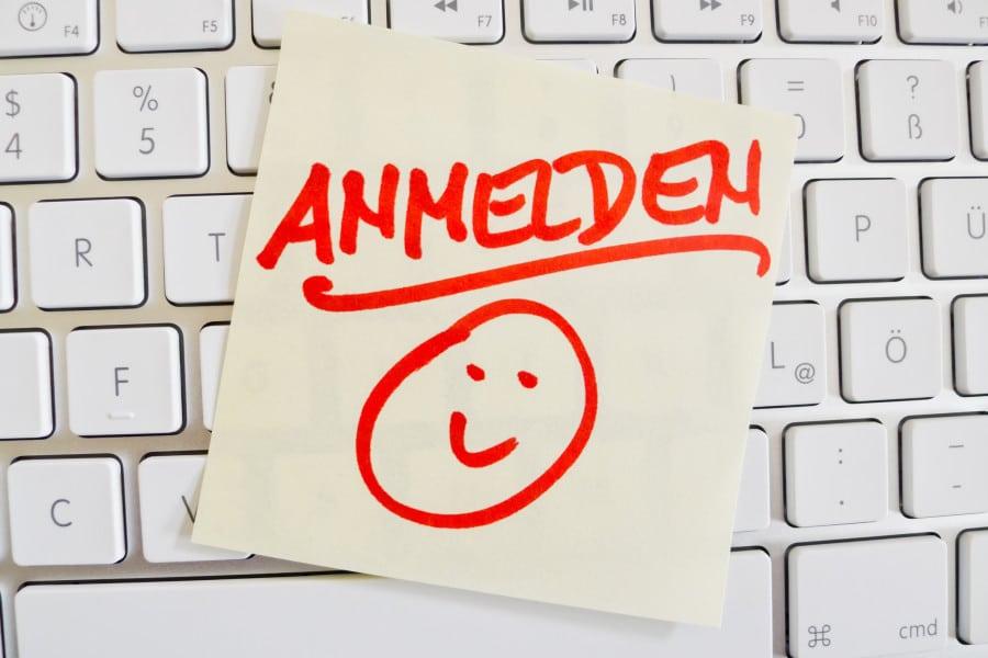 Ein Notizzettel liegt auf der Tastatur eines Computers zur Erinnerung: Anmelden